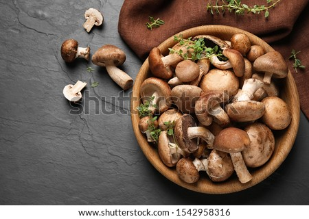 Different fresh wild mushrooms in bowl on black background, flat lay Foto stock ©