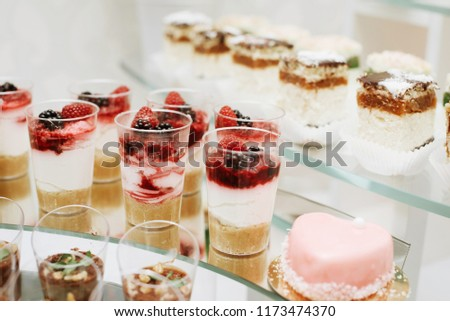 Different fruit desserts with fruits in glasses on the table. Restaurant presentation, food, party concept