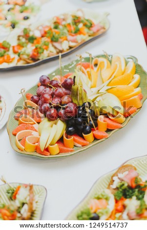 different fruits cut in portions on a plate, grapefruit, orange, grapes and pear