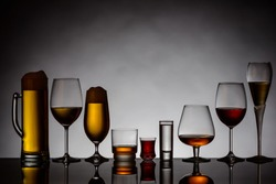 different glasses of alcoholic drinks backlit with reflection