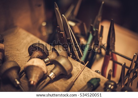 Different goldsmiths tools on the jewellery workplace