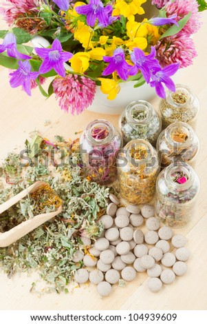 different healing herbs in glass bottles, flowers bouquet in mortar, tablets, herbal medicine, top view