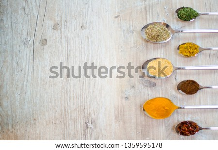 Different herbs in spoons on the side of a light wooden table. dried curry, dried garlic, dried tarragon