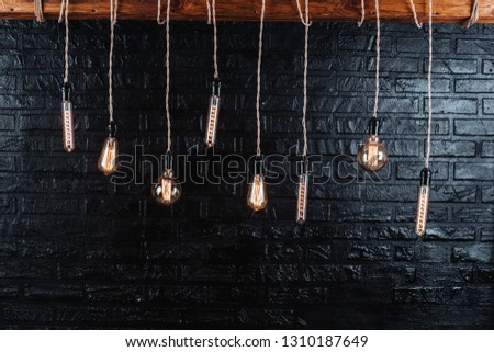 different incandescent bulbs against the background of the black mortar wall