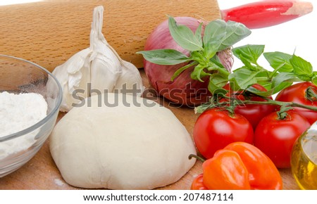 Different ingredients to make a pizza on a wooden board