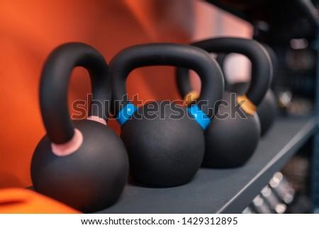 Different kettlebells. Different kettlebells lying on shelf for sportsmen in the fitness center