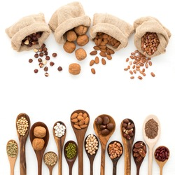 Different kind of beans and lentils in wooden spoon on white wood background. mung bean, groundnut, walnuts, macadamia, almond, soybean, red kidney bean, black bean, sesame,red bean, brown pinto beans