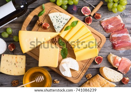 Different kind of cheese with wine, figs, walnuts, jamon