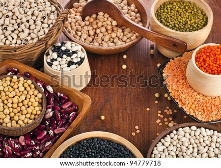 Different kinds of bean seeds, lentil, peas in dish on wooden desk