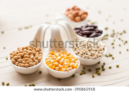 Different kinds of bean seeds, lentil, peas in dish on wooden table, macrobiotic food or healthy food Stock photo ©