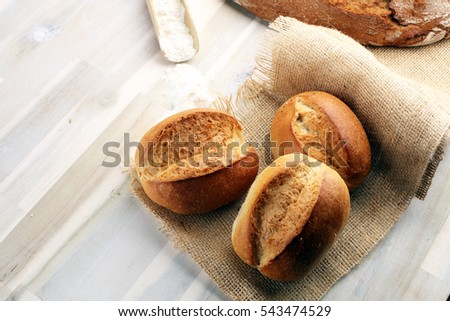 Shutterstock Different kinds of bread rolls on black board from above. Kitchen or bakery poster design.