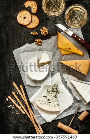 Different kinds of cheeses, white wine and snacks on black chalkboard background captured from above (top view). French tasting party or feast scenery.