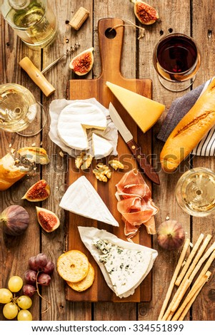 Different kinds of cheeses, wine, baguette, fruits and snacks on rustic wooden table from above. French tasting party or feast scenery.