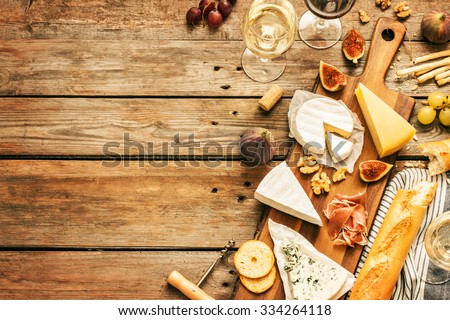 Different kinds of cheeses, wine, baguettes, fruits and snacks on rustic wooden table from above. French tasting party or feast scenery. Layout with free text space.