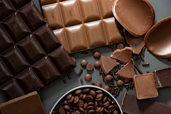 Different kinds of chocolates on dark gray background; milk and dark chocolates; cravings; sweets; temptation