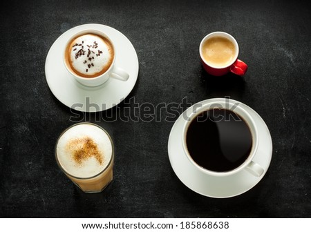 Different kinds of coffee on black chalkboard background. Cappuccino, espresso, americana and latte from above - cafe menu.