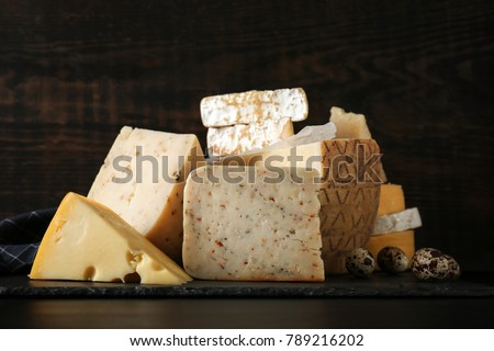 Different kinds of delicious cheese on wooden background