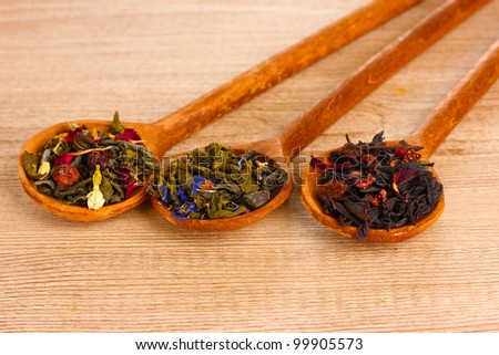 Different kinds of green and black dry tea in spoons on wooden table