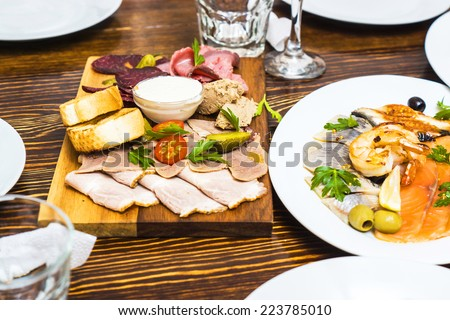 different kinds of meat on a wooden board in russian restaurant