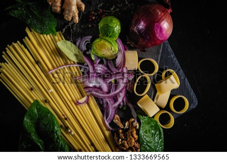 Different kinds of pasta background. Different kinds of pasta and tomatoes on wooden background. Different kinds of pasta spread over the table
