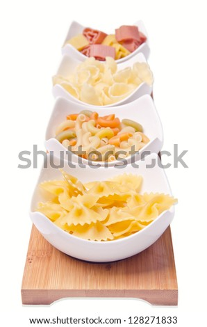 Different kinds of pasta in little white kitchen bowls.
