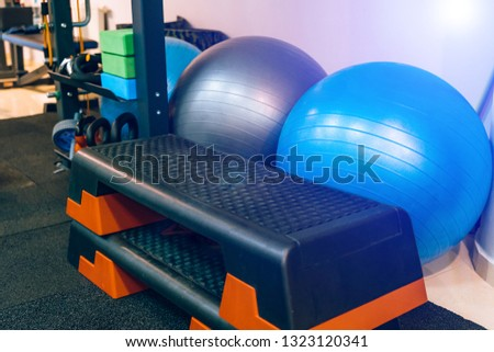Different kinds of sport equipment in the fitness club indoors. Plastic stands and fitness balls for doing workout in the gym #1323120341