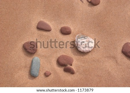 Different kinds of stones, including sandstone, lying on the sandy, beach