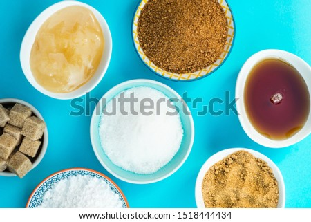 Different Kinds of Sugar and Sweeteners in the Bowls, such as coconut, pure cane, icing, maple syrup, dark brown soft sugar, honey, demerara cubes #1518444434