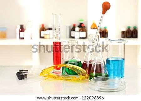 Different laboratory glassware with color liquid on laboratory background