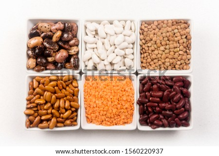 Different legumes seeds as beans and lentils are in white dishes on white background.