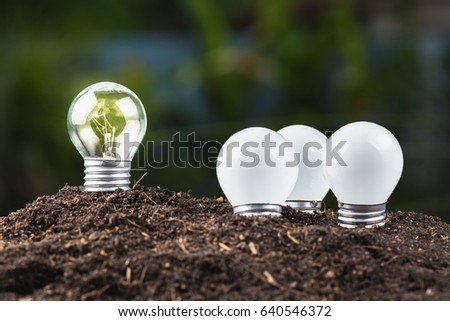 Different light bulb glowing outside the group