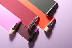 Different lipsticks on color background