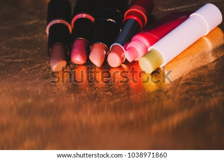 Different lipsticks. Used lipsticks. Nude lipsticks, lip balm. Close-up photo. Lipsticks laying down on golden surface. Colorful reflection. Lip care, beauty and fashion. Fashion and beauty blogger.   #1038971860