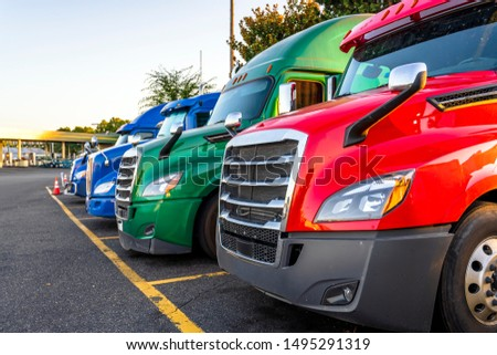 Different make and models big rigs semi trucks with semi trailers standing in row on truck stop parking lot for rest and comply with the movement according to the schedule for successful delivery #1495291319