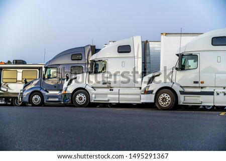Different make and models big rigs semi trucks with semi trailers standing in row on truck stop parking lot for rest and comply with the movement according to the schedule for successful delivery #1495291367