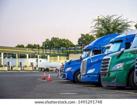 Different make and models big rigs semi trucks with semi trailers standing in row on truck stop parking lot for rest and comply with the movement according to the schedule for successful delivery #1495291748