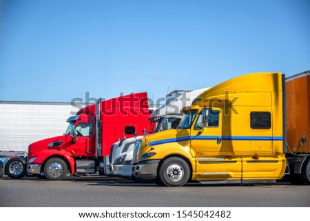 Different makes and colors of big rigs semi trucks with semi trailers standing in row on truck stop parking lot for truck drivers rest and adherence to the transportation schedule #1545042482