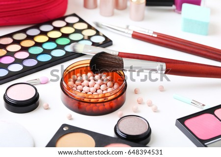 Different makeup cosmetics on white table #648394531