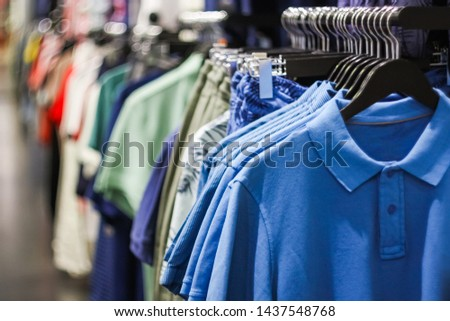 Different man's shirts sold in a clothing store. Male Clothes on Open Clothes Rail