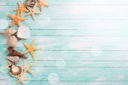 Different marine items in ray of light  on turquoise wooden background. Sea objects - shells, sea stars on wooden planks. Selective focus.