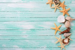 Different marine items on turquoise wooden background. Sea objects - shells, sea stars on wooden planks. Selective focus.