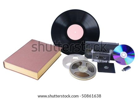 "Different mediums: big brown book, magnetic tape bobbins, audio cassette, video cassette, 3,5"" diskette, vinyl disk, USB flash drive, compact disk. They are isolated over white."