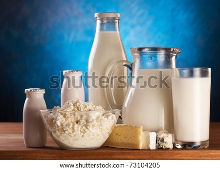 Different milk products: cheese, cream, milk, yoghurt. On a blue background.