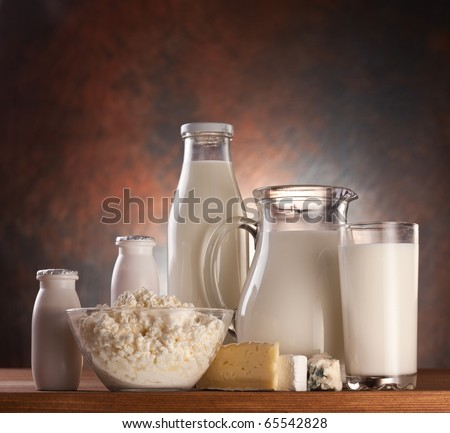 Different milk products: cheese, cream, milk, yohurt. On a brown background.