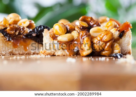 different nuts in a round tartlet, a round tartlet with nuts and dried fruits poured with caramel, the ingredients used in the made tartlet are hazelnuts, peanuts, dried apricots, dried plums, walnuts