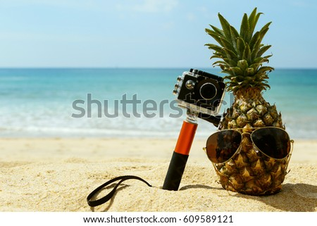 Different objects on the beach. Pineapple, sunglasses and action-cam.