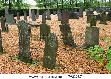 Different old tombstones on a graveyard in the autumn
