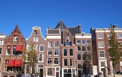 Different old traditional and narrow canal houses seen in the center of Amsterdam on a sunny day
