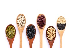 Different or various types of dry beans or dried legumes in wooden spoon isolated on white background. Whole grains ,healthy food and diet concept. Top view. Flat lay.