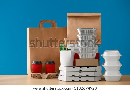 Different packages and carton cups on table against color background. Food delivery service #1132674923